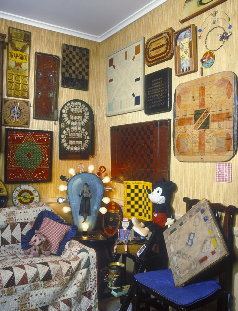 Stock Photo: 4053-10512 COLLECTIBLES - Display of vintage game boards on wall of family room, old Mickey mouse,  old carnival sign with light bulbs, sofa covered in vintage quilt, bamboo wall covering