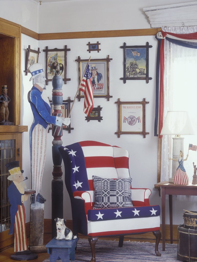 LIVING ROOM - Detail of corner area with wing back chair upholstered in red, white, and blue flag pattern. Patriotic theme, folk art statue of Uncle Sam, grouping of framed patriotic prints, patriotic drapes, folk art, country : Stock Photo