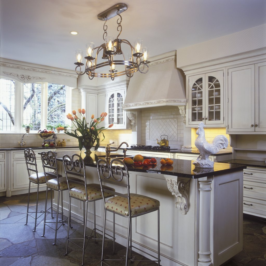 KITCHEN - Classic contemporary traditional design. Island with detailed corbels, iron barstools, subway tile , hanging chandelier, stone floor, black counters, tulips, white rooster, range hood with corbels, cornice white : Stock Photo