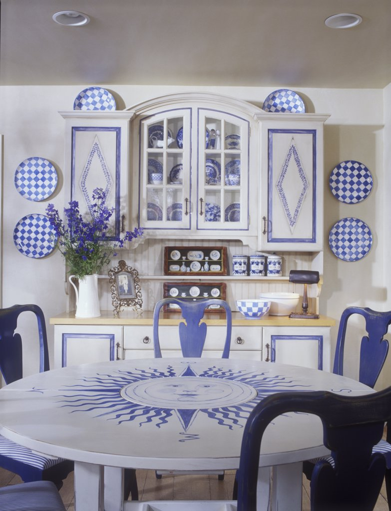 EATING AREA - In Family Room, round dining table with blue sun painted in center, blue painted Queen Anne chairs, blue and white checked plates, blue and white cupboard with glass display and diamond pattern on doors, delphinium vase in white pitcher, Swedish style cottage, : Stock Photo