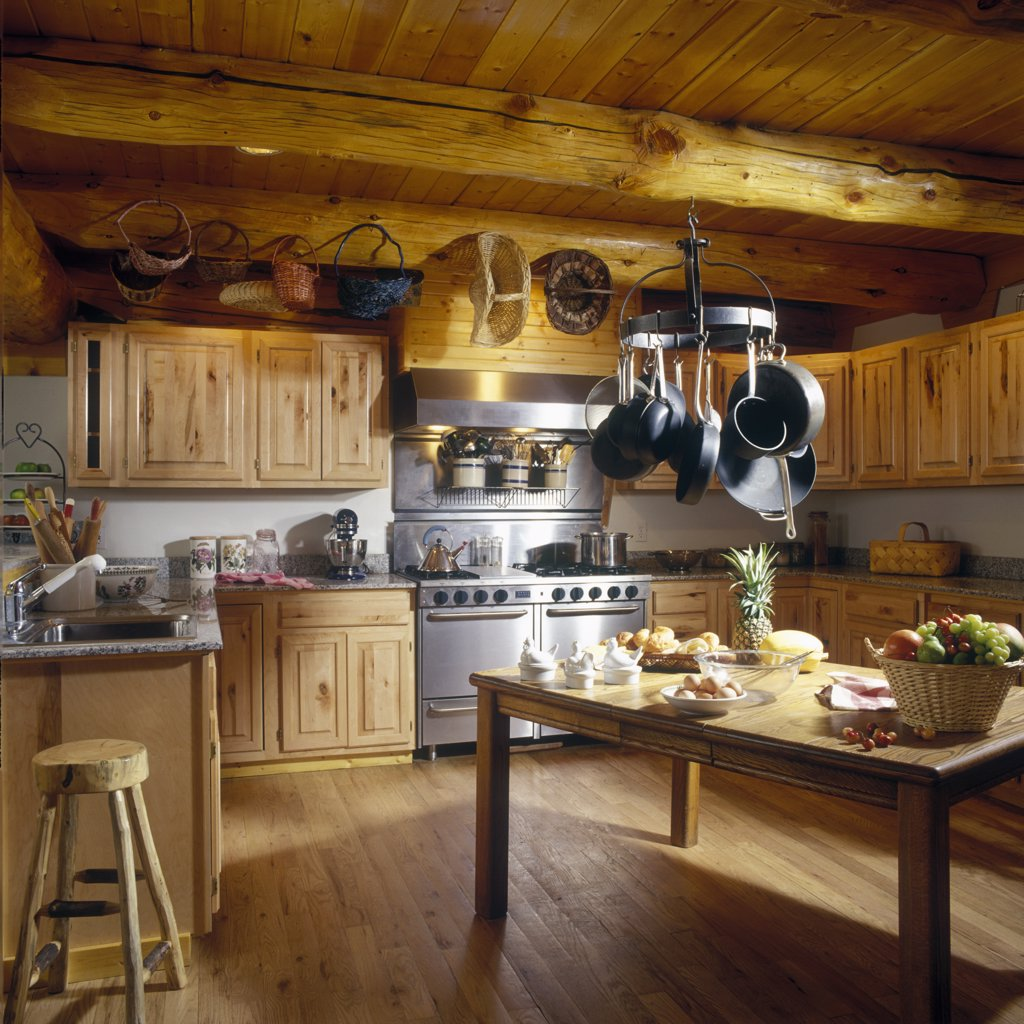 KITCHEN - Log home, exposed beam and wood ceilings, pine cabinets, stainless steel stove , hanging pot rack, table as center island, baskets hang from beams, : Stock Photo