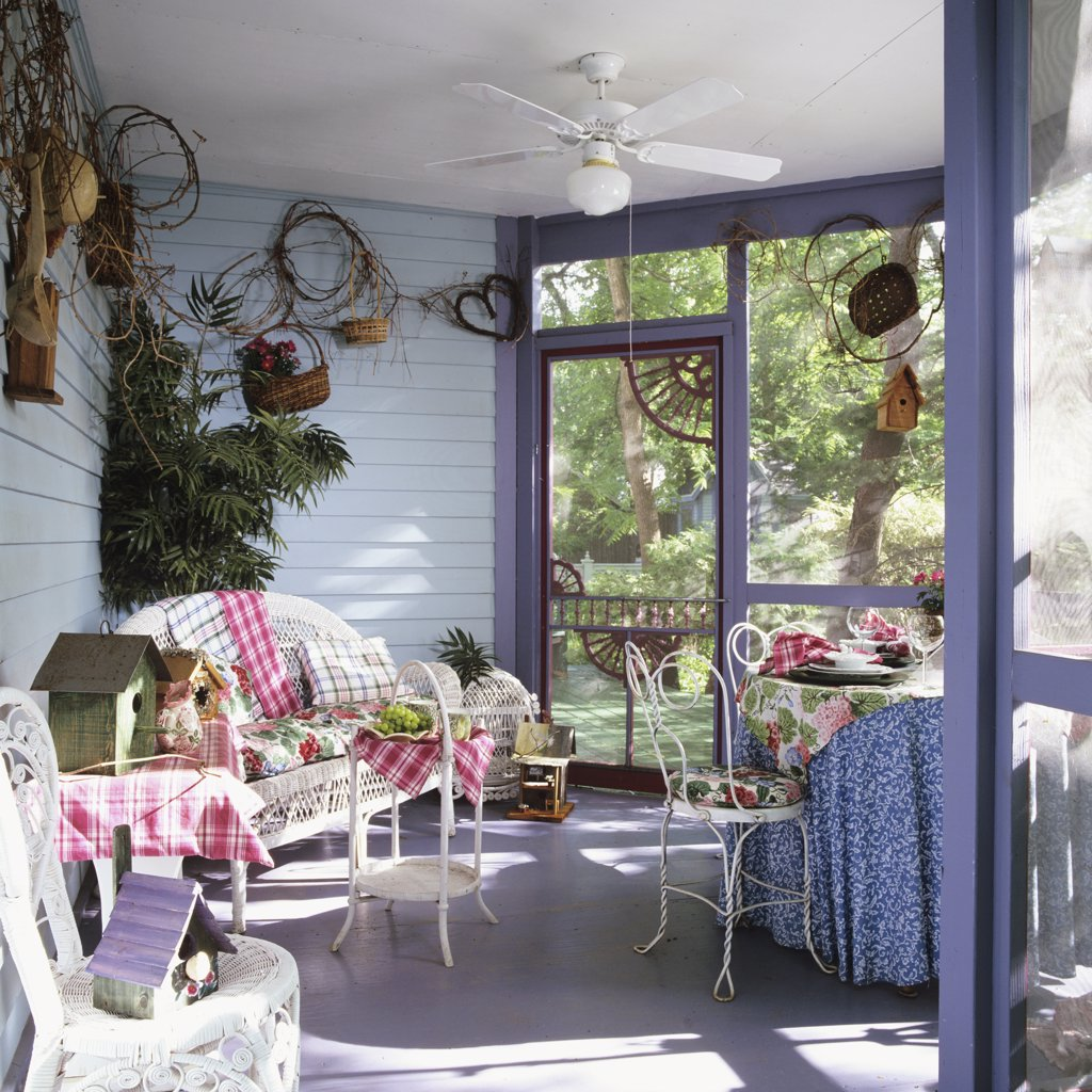 Stock Photo: 4053-10613 PORCH - Corner of screened porch with wicker couch. Birdhouses. Gray walls, soda fountain chairs, skirted table, grapevine tacked up on walls, ceiling fan