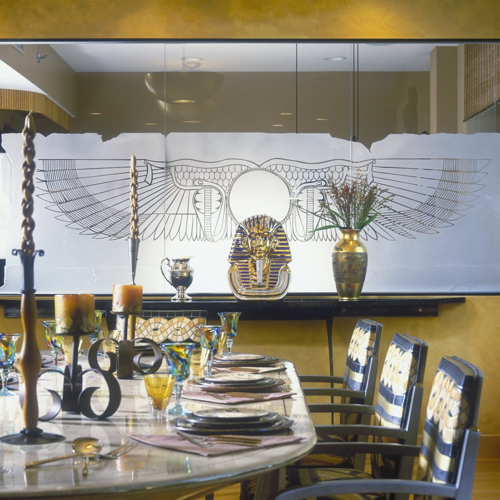 DINING ROOM - Etched glass wall  Egyptian themes, gold walls, modern and sleek furniture, Tutankhamen head, art glass wine glasses, artsy candlesticks : Stock Photo