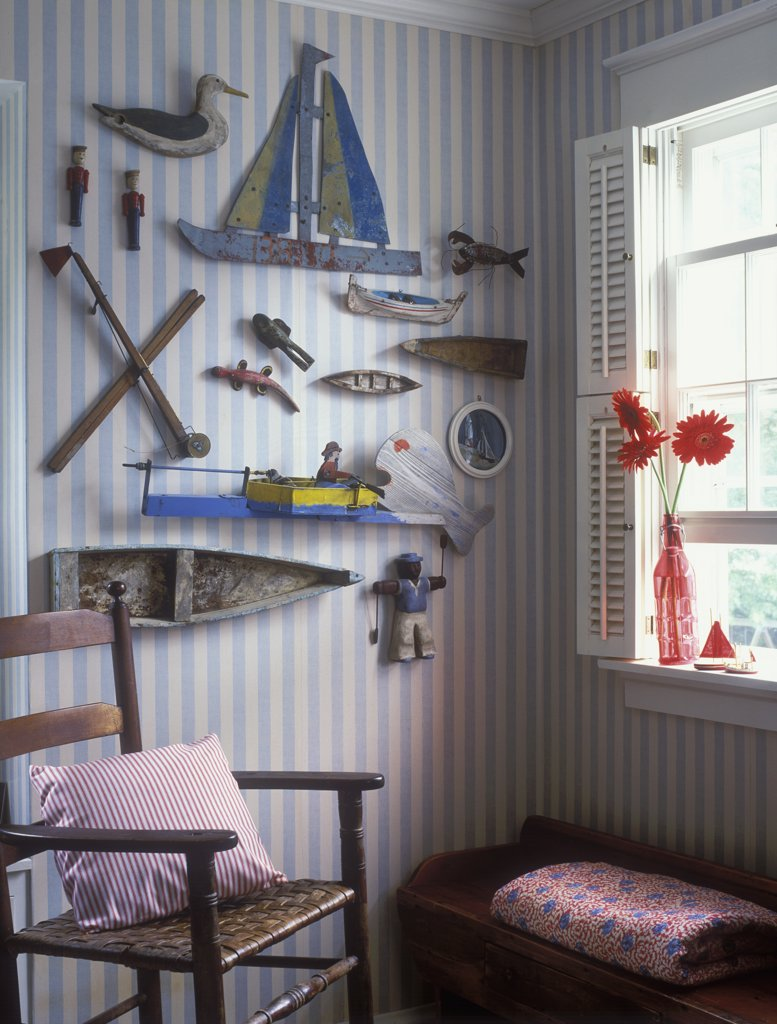 COLLECTION DISPLAY- Nautical theme, vintage boat models, antique toys, wall display, striped wallpaper, gerberas in rd glass vase on window sill, shutters, wooden arm chair : Stock Photo