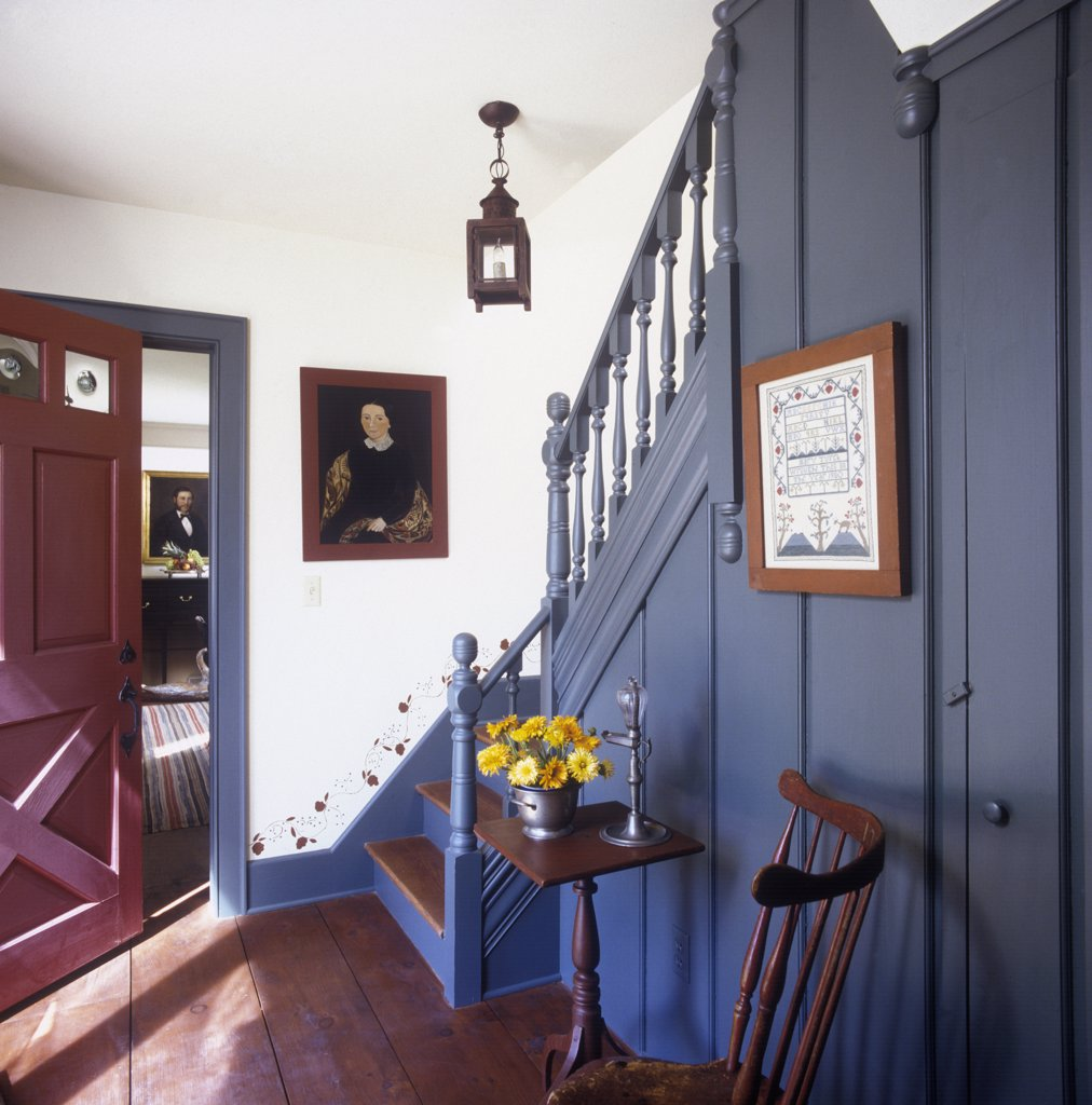 Stock Photo: 4053-10643 STAIRWAYS: Front hall of Colonial period style home, blue painted wood work on stairway, three legged candle table with pewter bowl of flowers, Windsor chair, stenciling along baseboard up the stairs, open red front door with bottle glass windows , portrait painting