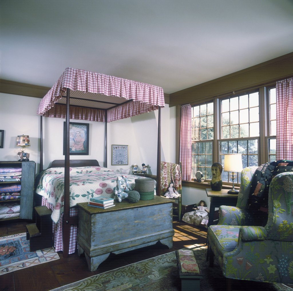 BEDROOM: Colonial  girls room, checked canopy and curtains, antique weathered trunk with a bracket foot, wing chair with crewel fabric, quilts stacked in a weathered cabinet, various dolls, shaker boxes, : Stock Photo