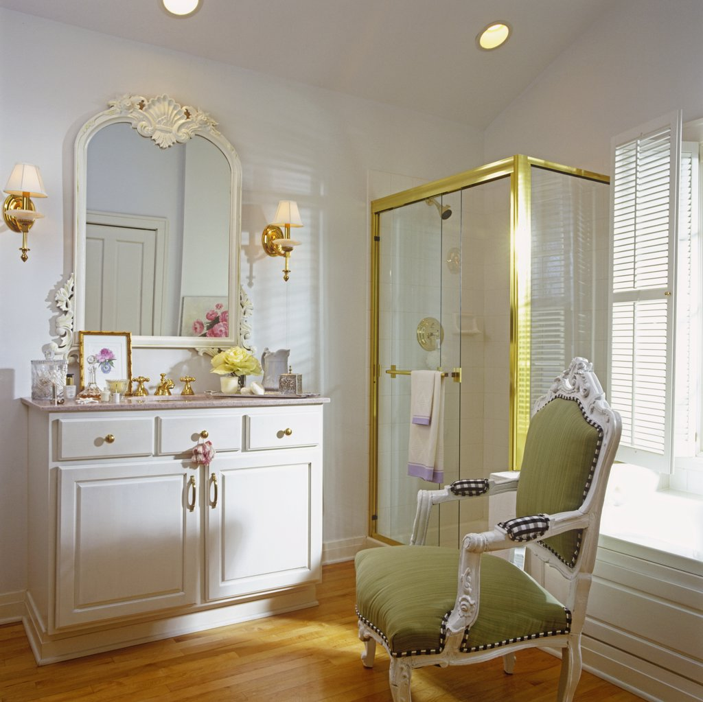 BATHROOMS: Sink in white chest, white walls, glass shower stall, brass framing. King Louis style arm chair with sage green seat and back rest. Wood floor, sconces. : Stock Photo