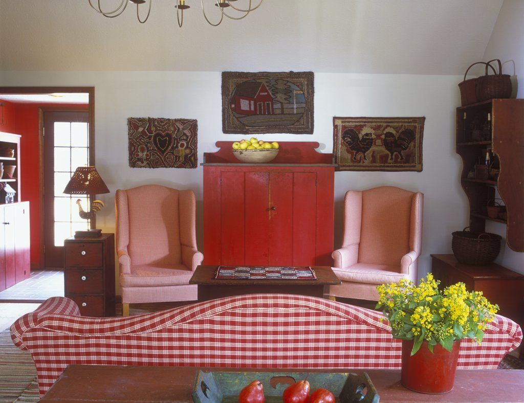 COLLECTION DISPLAYS - Hooked rugs hang above bright red primitive cabinet, checked red and white wing back chairs and sofa. Clean country Primitive look in a living room, rooster lamp, maple syrup bucket filled with yellow flowers, yellow apples in wood bowl, red pears in painted blue wooden tray. camel back sofa : Stock Photo