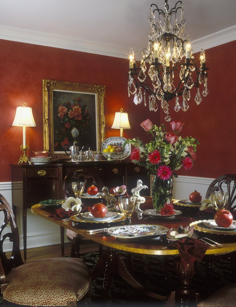DINING ROOM - White wainscoting red walls. Chandelier, sideboard with lamps, floral painting sits on top of sideboard, tea set, gerbera and rose floral arrangement, Duncan Phyfe dining table, pomegranates, formal : Stock Photo