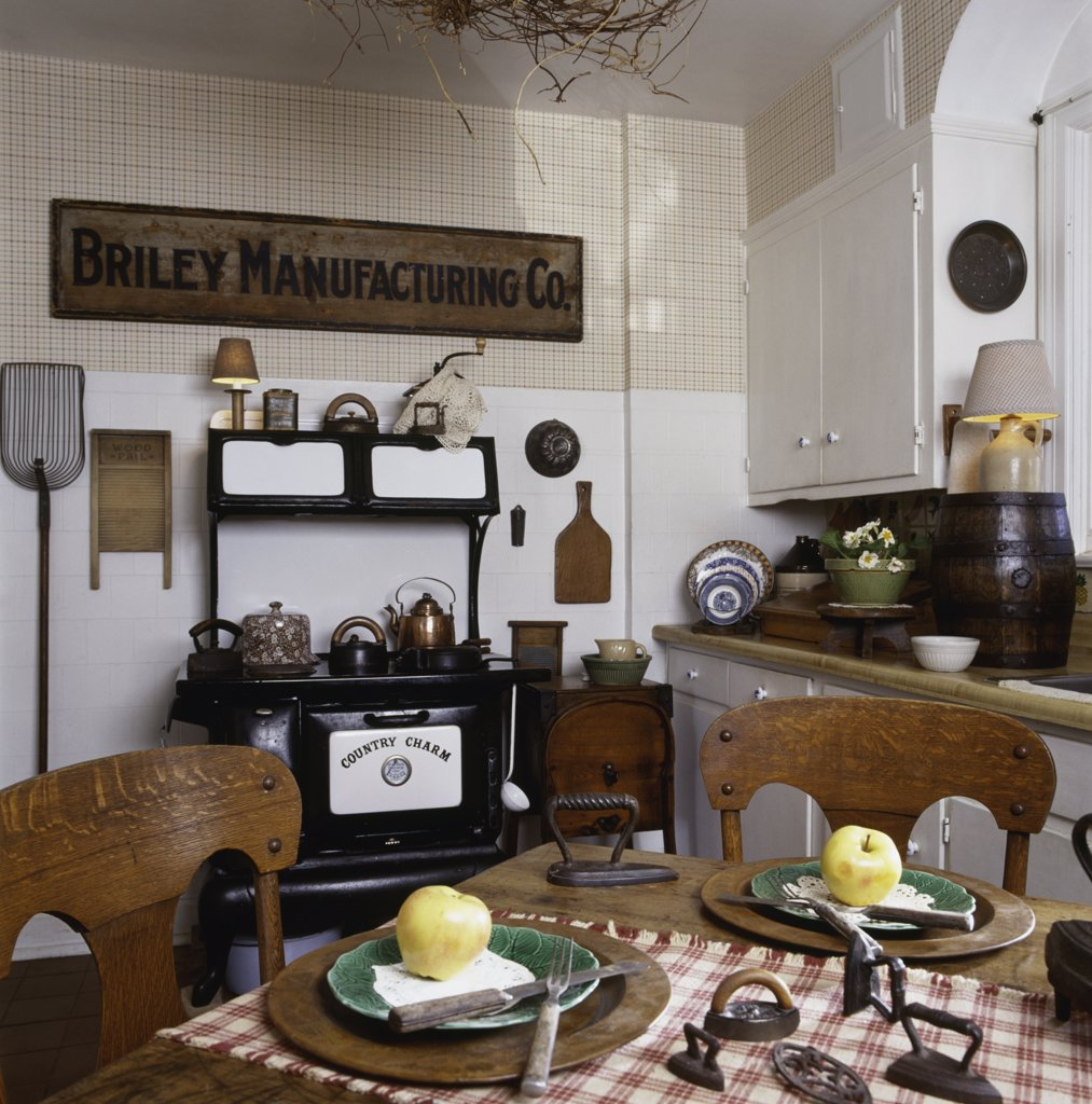 KITCHEN : Vintage Country, new electric cast iron stove, oak farm table and chairs, antique iron collection, nostalgic kitchen collectibles : Stock Photo