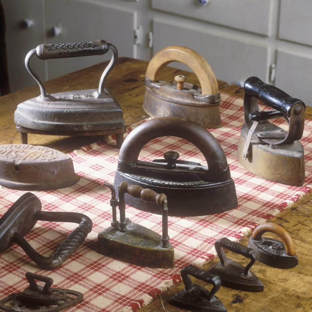 Stock Photo: 4053-10677 COLLECTION DISPLAYS - Antique irons on woven checkerboard table runner.