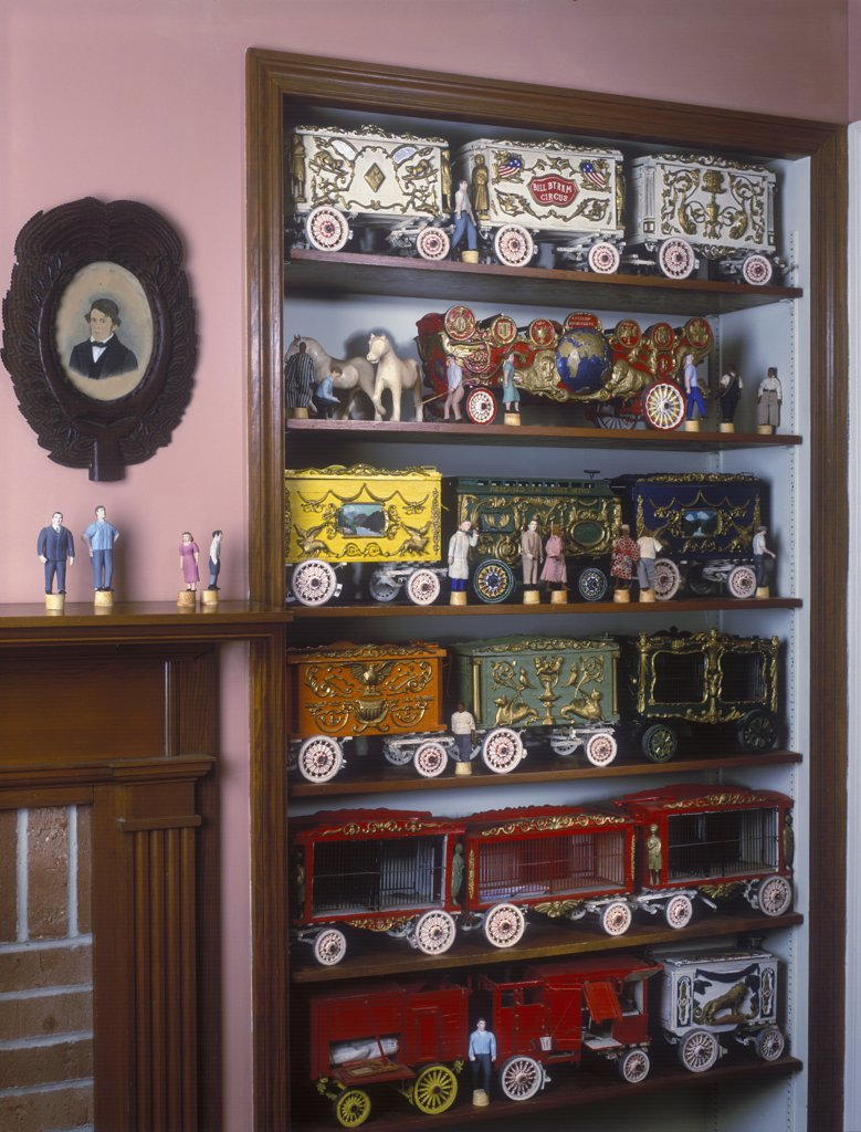 COLLECTIONS DISPLAY - Colorful collection of Circus Wagons displayed on recessed shelves next to fireplace, made from 1940 through 1960's. Some hand carved. : Stock Photo