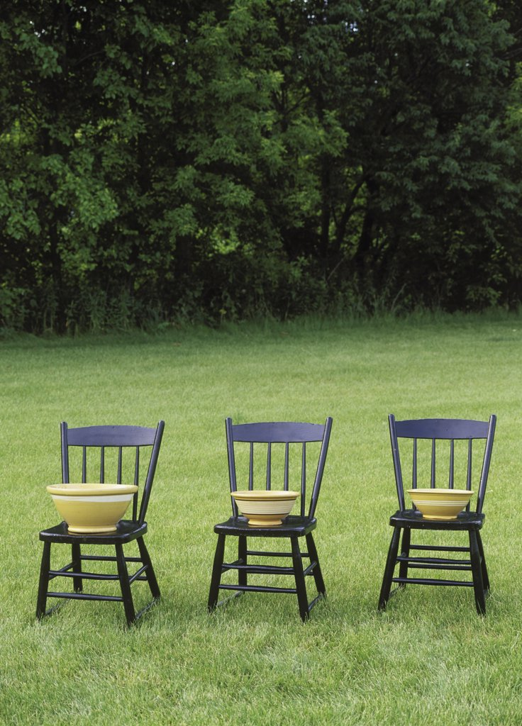 CHAIRS ON LAWN - Collectible bowls, slip band yellow ware : Stock Photo