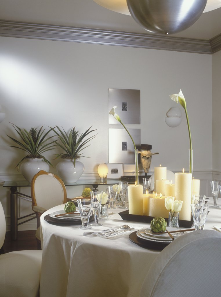 Stock Photo: 4053-10756 DINING ROOM  - Contemporary, eclectic. Tablecloth, , glasses, artichokes, tray of various different height candles, calla lilies, glass side table with two ceramic white pots with pineapple plants, silver framed artwork, silver molding, white walls and dado, African mask, Kidogo, chopsticks, Louis style chairs