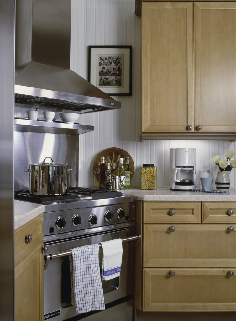 Stock Photo: 4053-10808 KITCHENS: Contemporary Country style kitchen with stainless steel stove and hood, beaded board with white paneling and maple stained cupboards