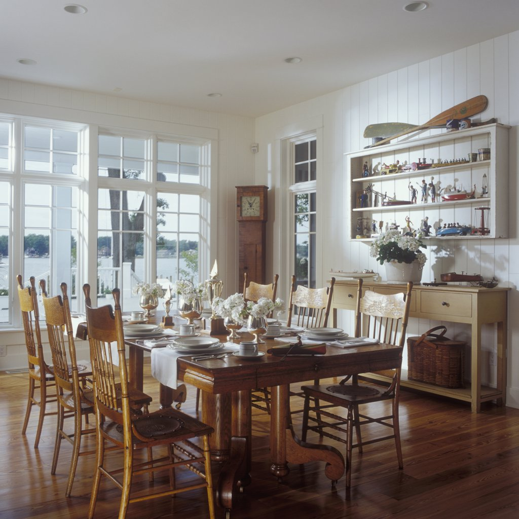DINING ROOMS - 1930's oak table, early 20th century dining chairs with pressed leather seats. Toy boat collection on shelves. View of lake. Case clock, painted paneled wall, transoms, silver trophy vases, white phlox, wood floors : Stock Photo