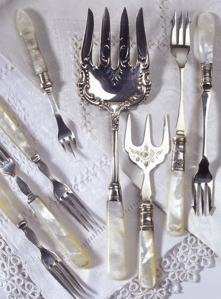 Stock Photo: 4053-10825 COLLECTIONS - Mother-of-pearl handles, sterling silver serving pieces on antique linens, iridescent, early 1900's.