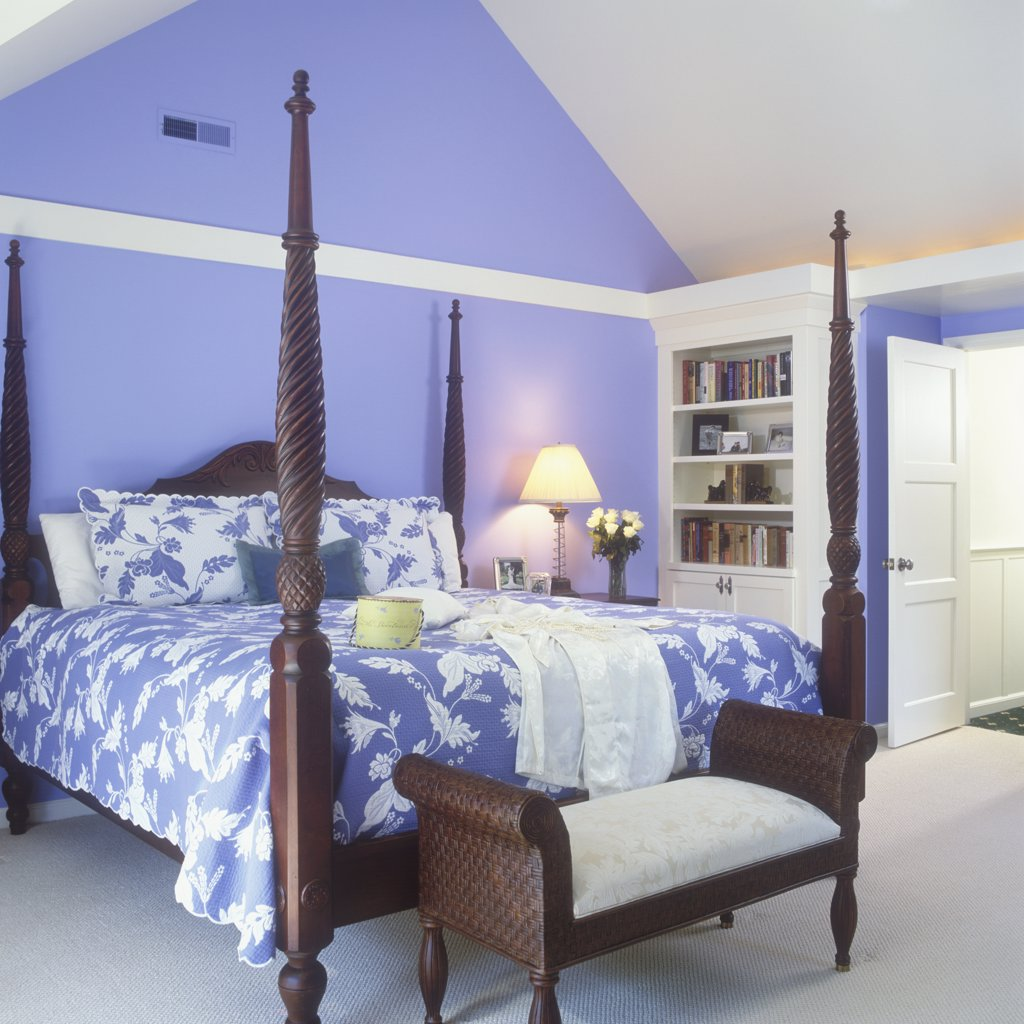BEDROOM -vaulted ceiling, periwinkle blue walls with quilt spread to match, dark wood  four poster bed, plantation style, bench bookshelves. : Stock Photo