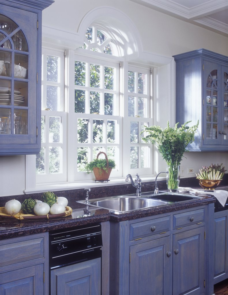 Stock Photo: 4053-10883 KITCHENS - Palladian style window over sink, flanked by teal raised paneling glass front cabinets, double bowl stainless steel sink, granite countertops, ogee edge, paint washed wood cabinets, white onions and artichokes, asparagus, snapdragons,