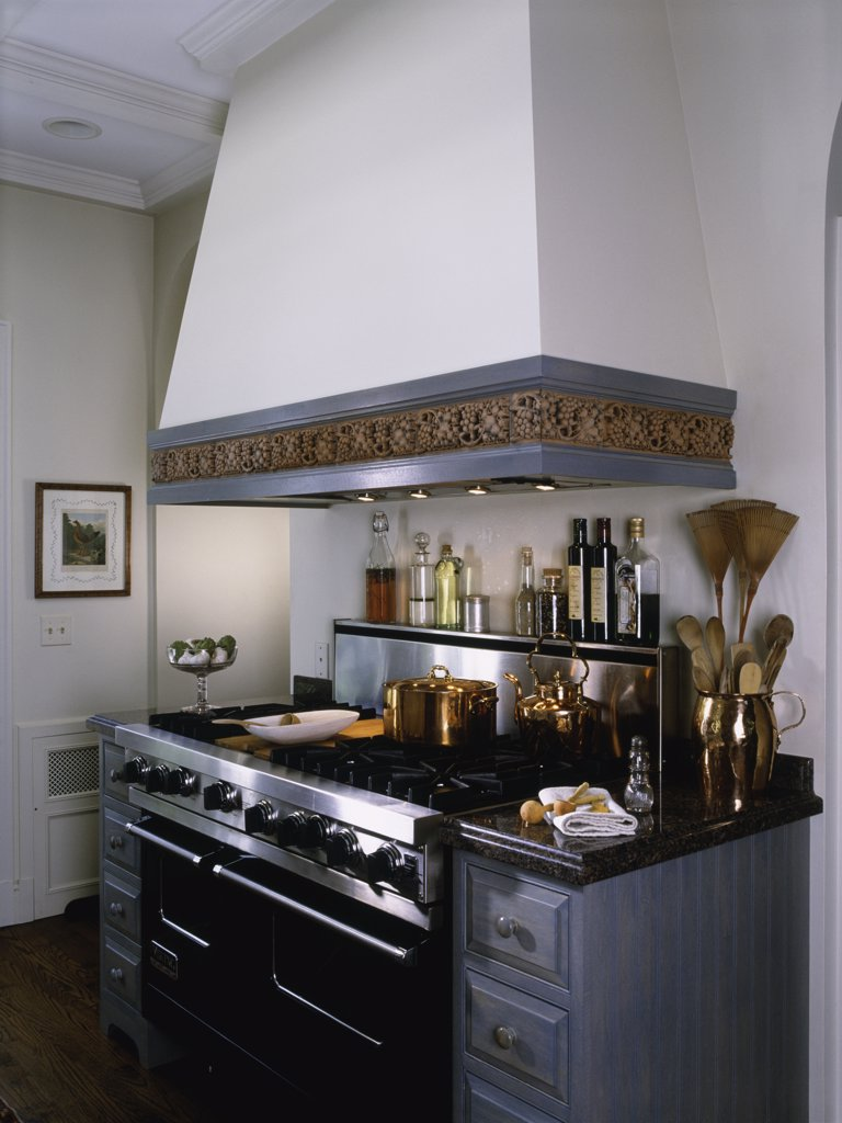 Detail of ceramic border of hood over stainless professional range, drawers, granite counter top : Stock Photo