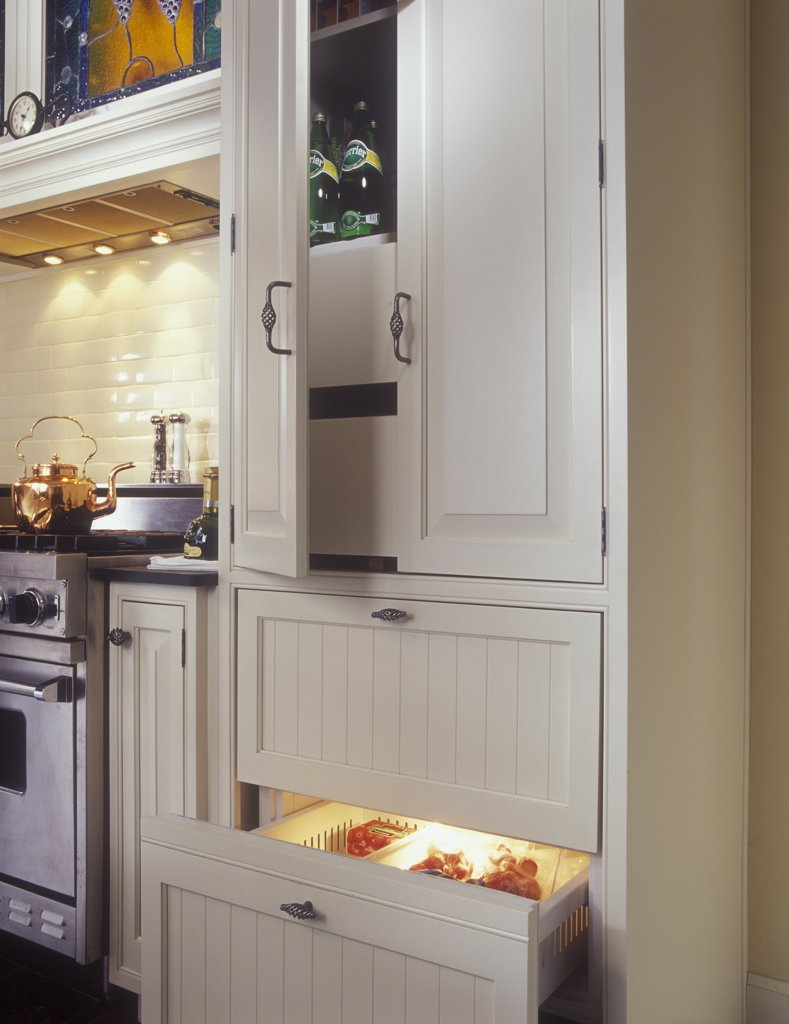 KITCHENS - Pantry on top of SUB-ZERO 700 series base freezer. Narrow pullouts on either side of range, white and stainless steel, raised panel cabinet doors, subway tile, copper tea kettle, : Stock Photo