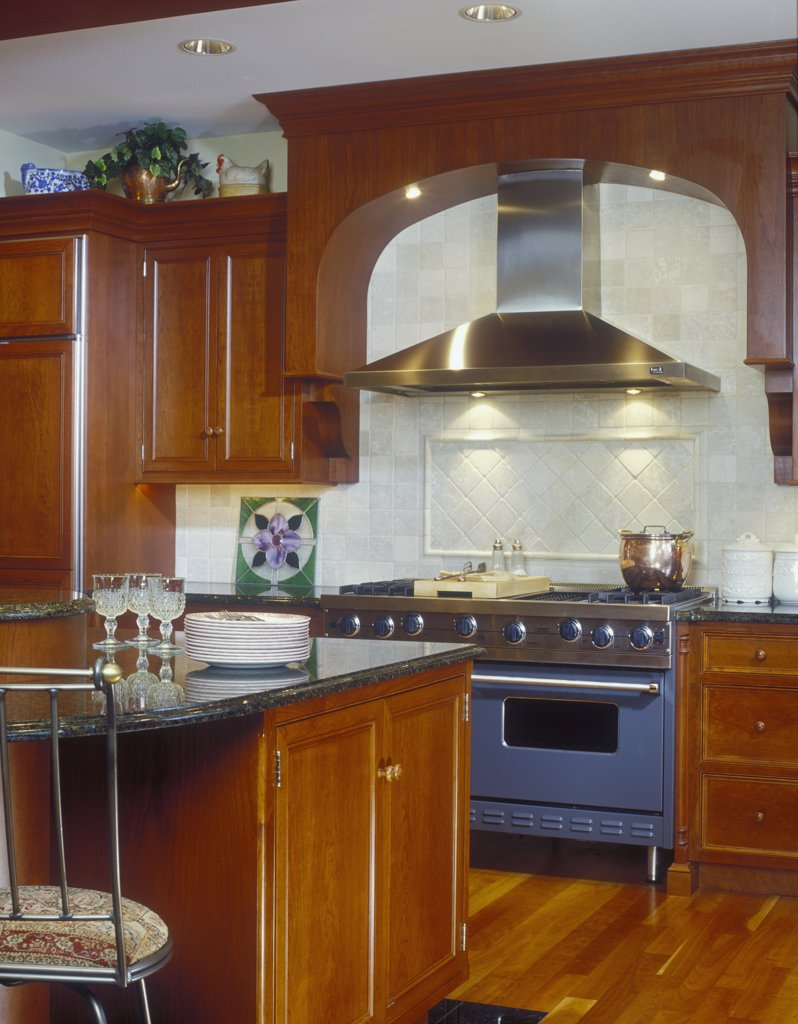 KITCHEN - Partial view of island and stove area with exhaust hood, commercial stainless steel, cherry wood cabinetry, granite tops. : Stock Photo