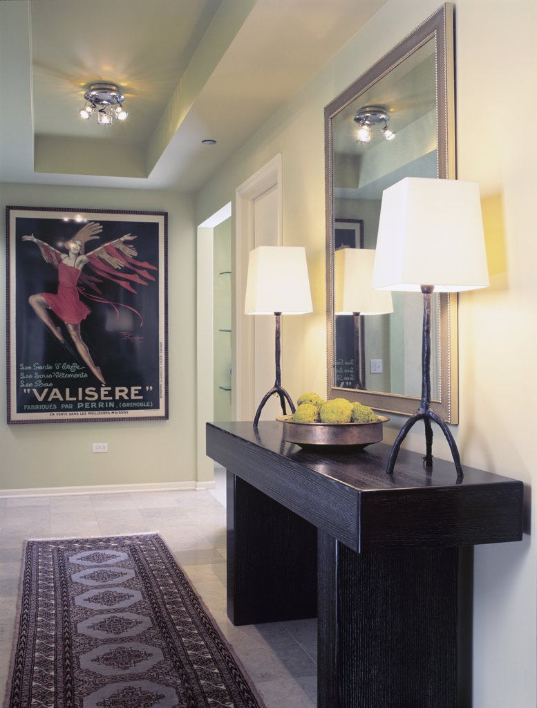 ENTRY HALL: contemporary mix of modern, and classic accents, oriental rug, Vintage French poster, large mirror to the right with contemporary table lamps, copper bowl of hedge apples : Stock Photo