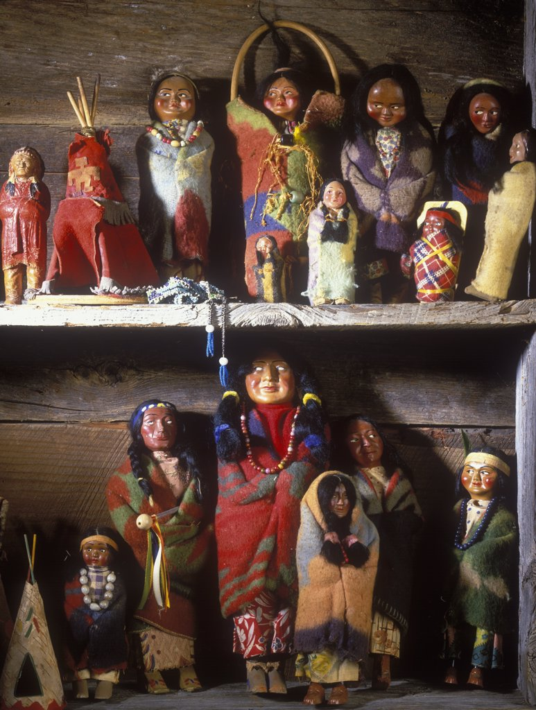 COLLECTION DISPLAYS - Vintage Native American dolls on display on shelves in rustic log home. Very colorful. : Stock Photo
