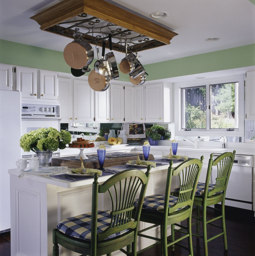 Stock Photo: 4053-10976 KITCHEN: with mirrored backsplash to create the illusion of space, white cabinets,, wrought iron hanging pot rack,  kitchen island cooking and eating area, green French provincial bar stools
