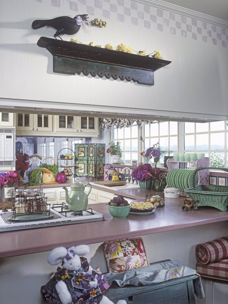 KITCHENS: View through 'pass through,' opening shows stovetop and sink, cottage style, vintage Jade-ite, wall shelf with carved crow, bunny in costume. : Stock Photo