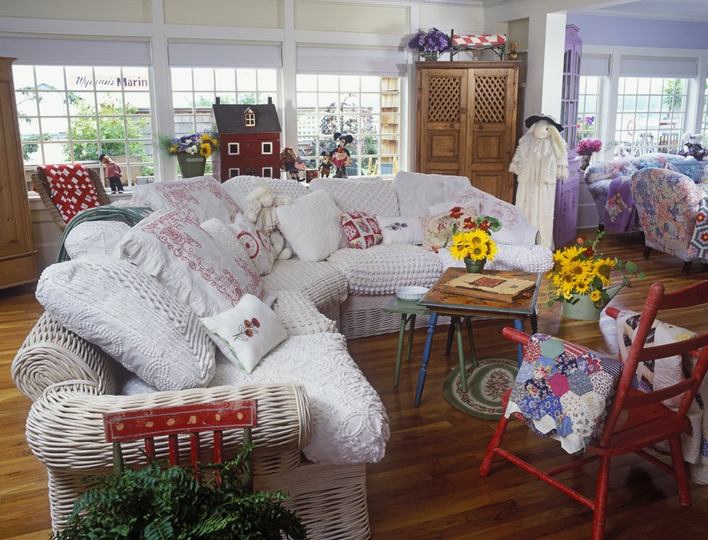 LIVING ROOMS - 'L' shaped room, lots of vintage fabrics on pillows, cottage style, white Wicker sofa with white chenille bedspread covered cushions, quilts, doll house. : Stock Photo