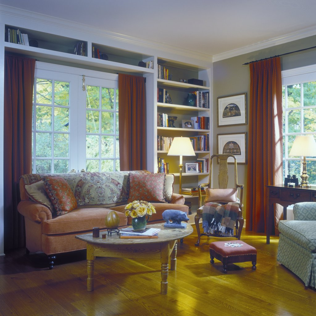 SITTING ROOMS - Traditional with French Country influence, coral couch with pillows, built in book shelves, French doors, red drapes, wood floor. : Stock Photo
