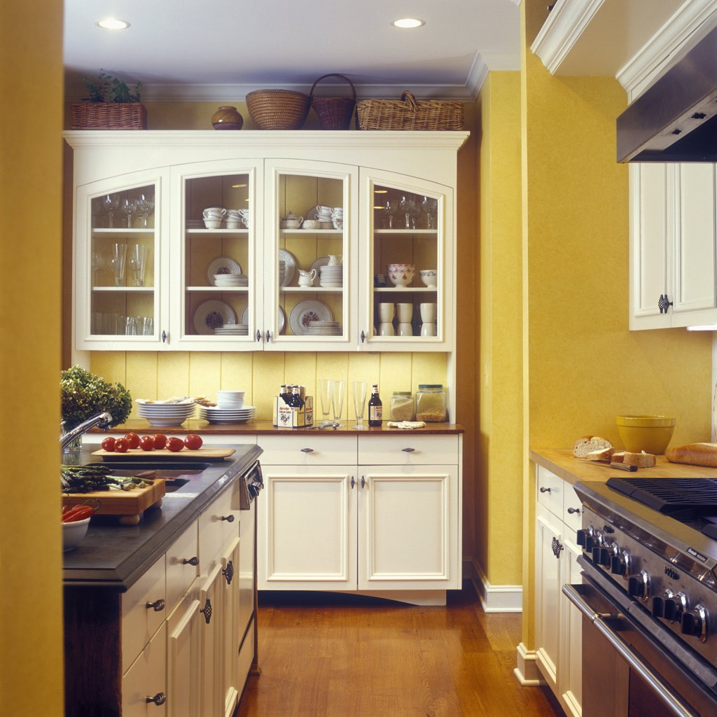 KITCHENS - Yellow walls with custom made white cabinets, glass doors, wood floor, island made from antique pine hutch, farmhouse style, molding, furniture style cabinets, tomatoes on cutting board, wood counters, ogee edge : Stock Photo