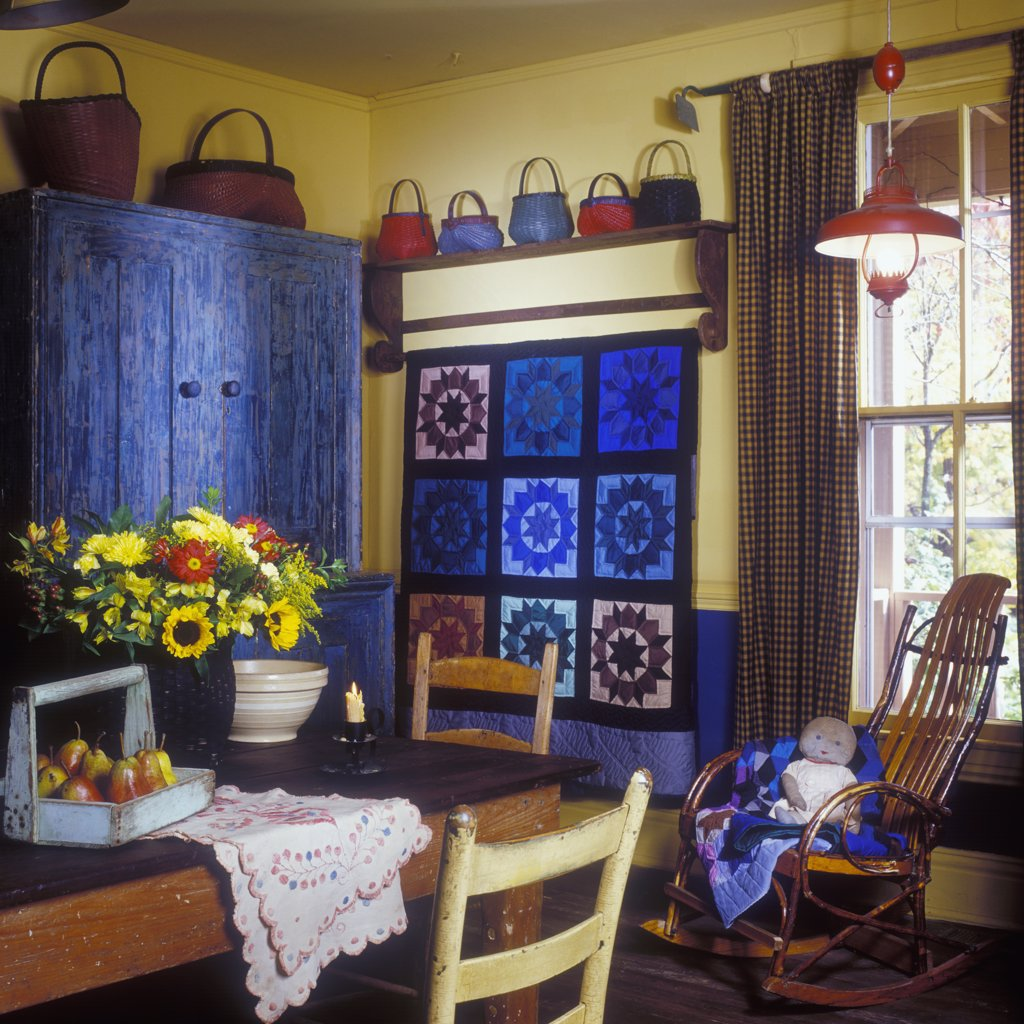 Stock Photo: 4053-11065 DINING ROOMS - Country charm, yellow walls, weathered step back armoire, colorful baskets on display. Amish quilt in blue hues hangs on wall. Hoe curtain rod.