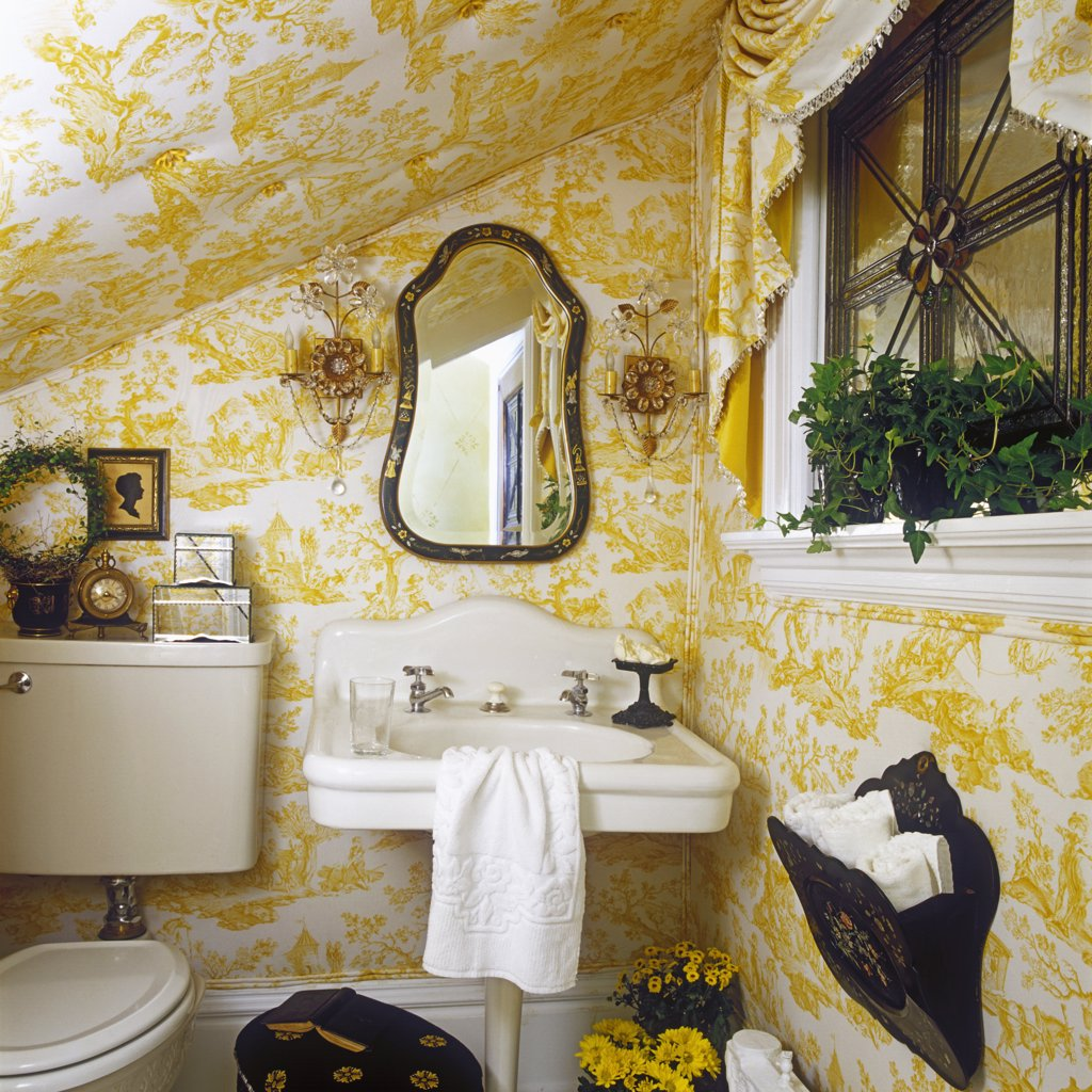 Stock Photo: 4053-11069 BATHROOMS: Under stairs room, French style, upholstered pale yellow and white toile scene, white vintage pedestal sink, crystal and glass sconces, swag valance, leaded glass window, black accents with yellow and white.
