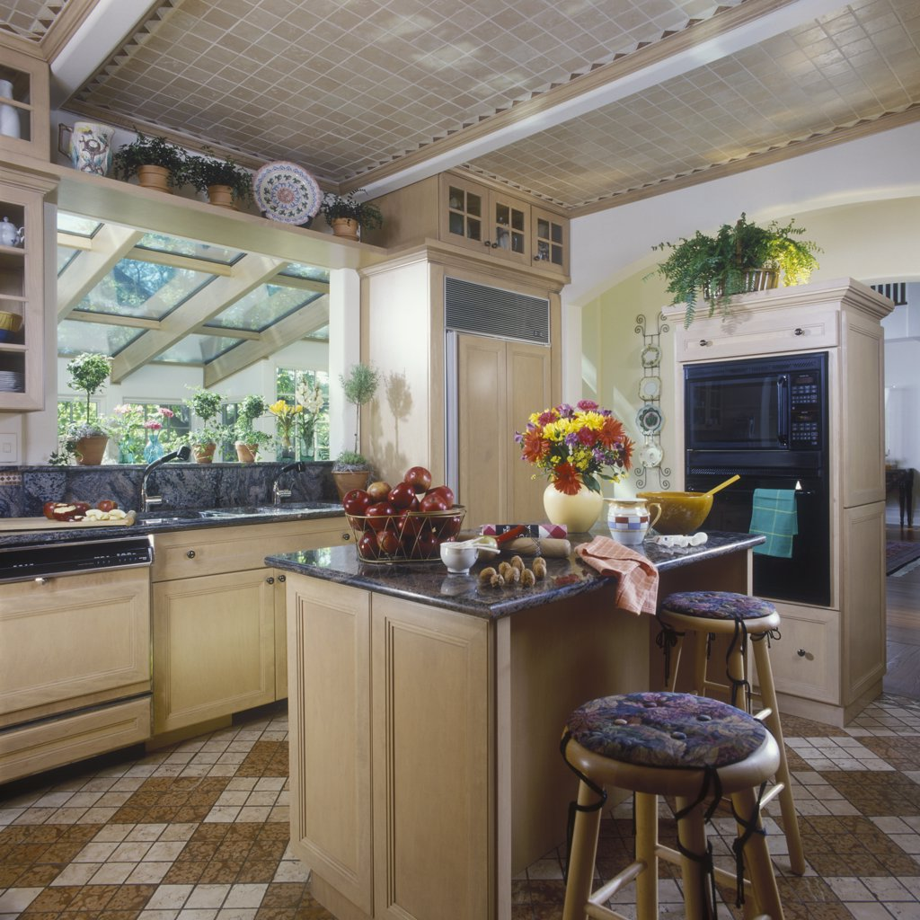 KITCHENS: Light color wood cabinets, light tan ceramic tile ceiling, granite countertops, view towards island and sink area, topiaries on ledge, tile ceiling, pass thru to sunroom : Stock Photo