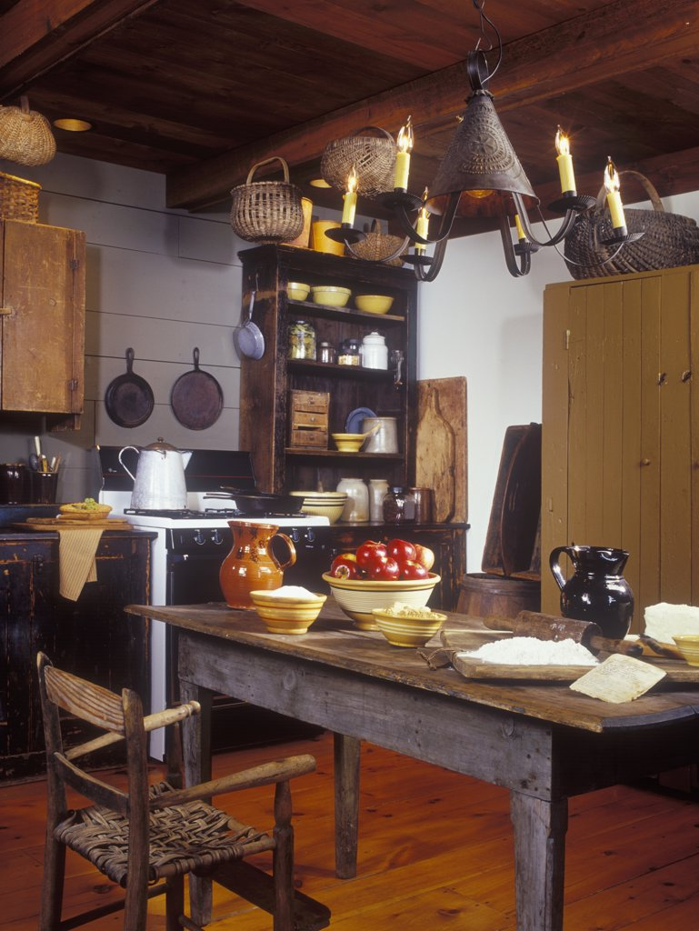 KITCHENS - Early American Primitive look to a new home. Flea market finds, weathered pieces, yellow ware baskets, pierced tin light fixture, exposed beam ceiling, farm table with baking supplies for apple crisp or pie, antiques, nostalgic : Stock Photo