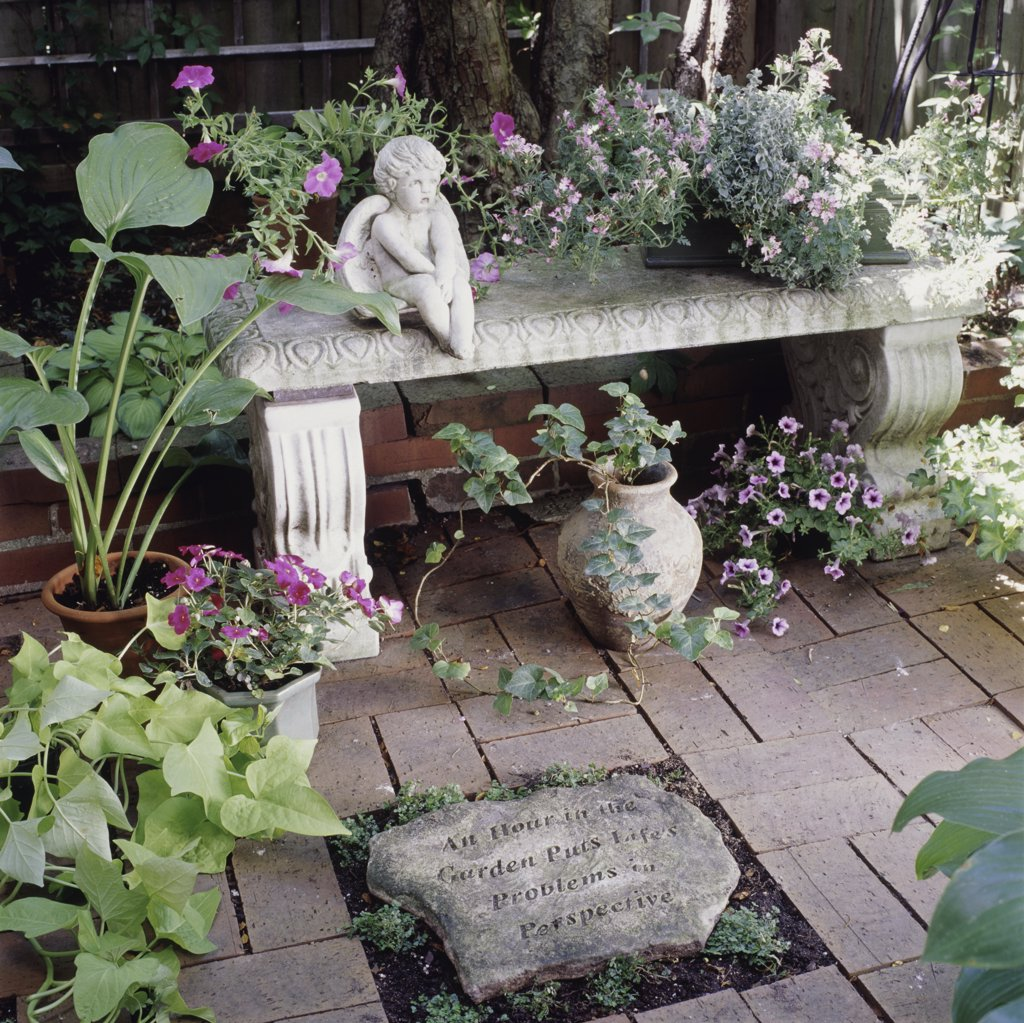 Stock Photo: 4053-11087 Garden with carved stone surrounded by pos of blooming flowers such as petunias and begonias, stone angle