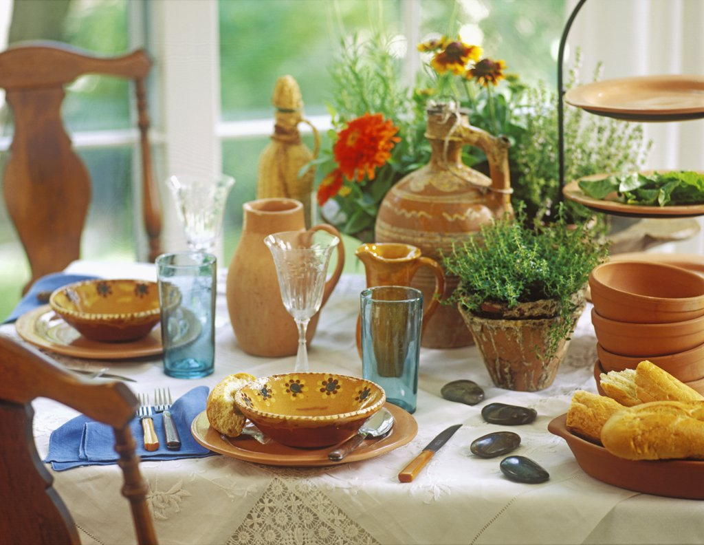 COLLECTIONS - DISHES: Handmade Terra Cotta pottery creates a nice tablescape, rustic country look. Herb plants and flowers as a centerpiece, vintage white table linens, European pottery jugs, pine pitch pots , orange zinnias, stylist Pillar Simon. : Stock Photo