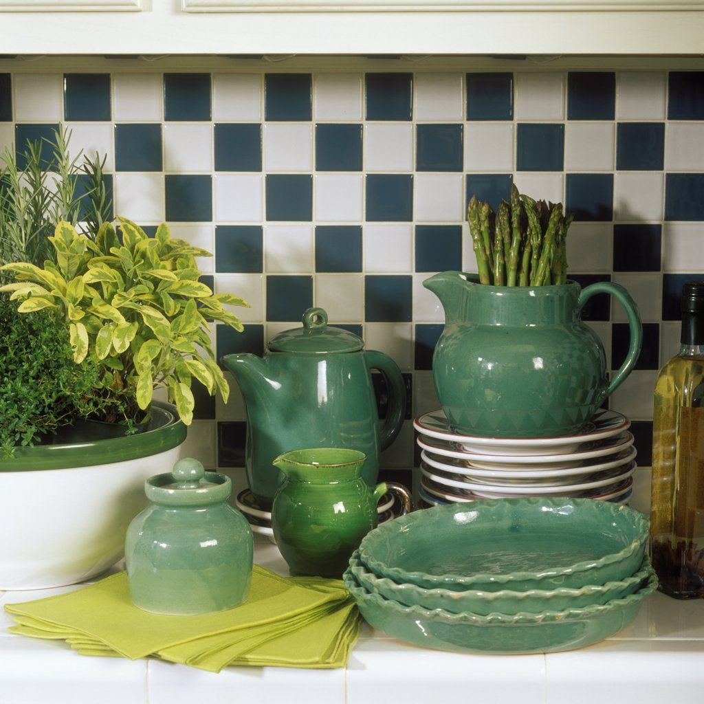 COLLECTIONS - DISHES: Handmade pottery from Berea, KY. Dark green bowls, pitcher, sugar & creamer sit on a kitchen tile counter. : Stock Photo