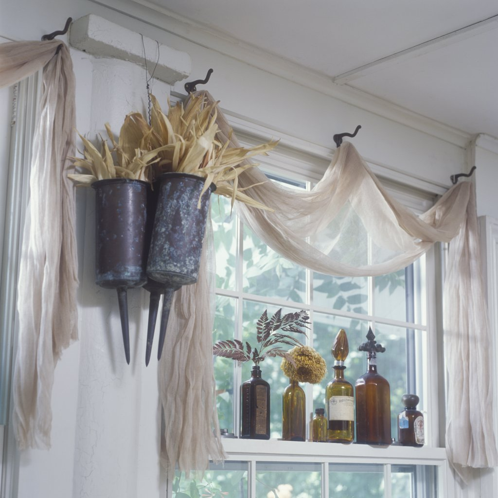 WINDOW TREATMENTS: Unique, Scrim (a net like fabric) valance, old coat hooks serve as drape points for scarf valance, copper funeral urns on left filled with cornhusk, brown colored bottles on window sill : Stock Photo