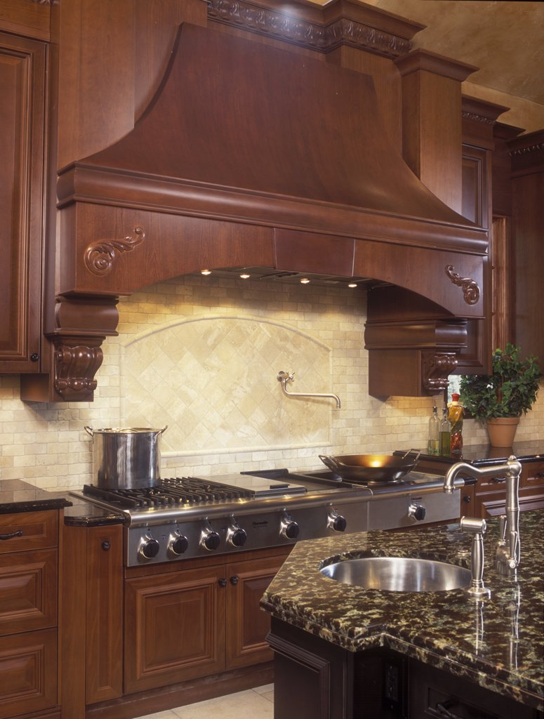 Stock Photo: 4053-11188 KITCHENS - Large stove top area, grill, marble counters, rich wood cabinetry, high end, large elaborate wood exhaust hood, beige tile back splash, hot water spigot, wok, corbels, prep sink in foreground, less propped