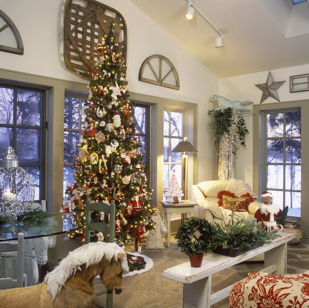 Stock Photo: 4053-11229 CHRISTMAS : Sunroom with a Christmas tree, white, grey and red, bench used as coffee table, fresh Christmas greens, rocking horse, architectural salvage on walls, horse weathervane sits on top of an architectural column,
