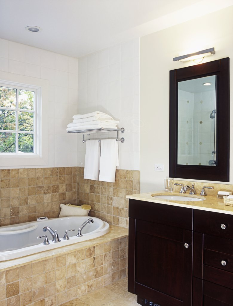 Stock Photo: 4053-11288 BATHROOMS: Whirlpool tub with beige/tan ceramic tile surround. Towel rack over tub, partial view of dark wood  sink vanity on the right, with tall wood framed rectangular mirror over sink.