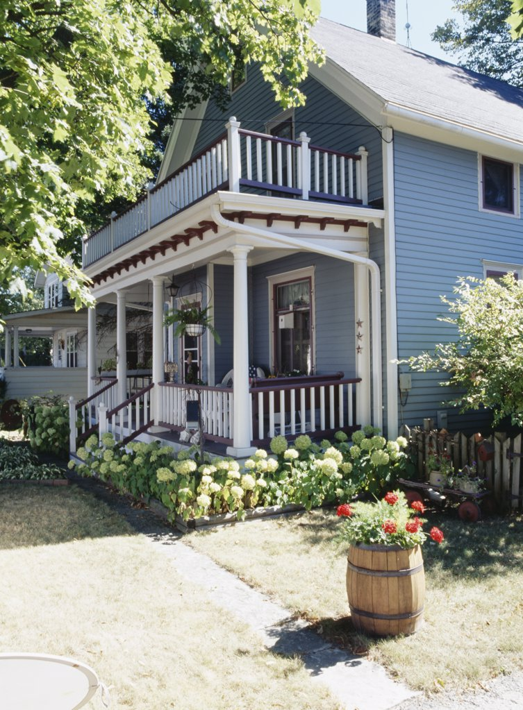 EXTERIORS: Two story single family farmhouse, two story porch, trimmed in white and burgundy, hydrangeas surround base, barrel filled with geraniums, house next door can be seen : Stock Photo