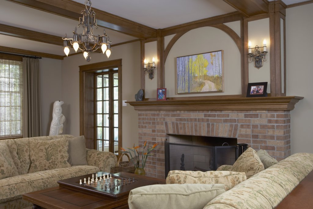 FIREPLACES: Monochromatic prairie style with traditional style, floral sofas face each other in front of a brick fireplace, arched wood trim and box beams, arts and crafts sconces and chandelier, chess set, birds of paradise in vase : Stock Photo