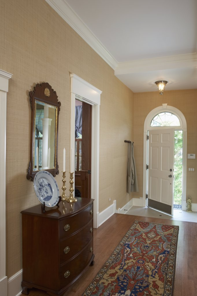 ENTRY HALLS: Traditional , wood floor with runner, tan sea grass wallpaper, white trim work, antique Georgian style chest and mirror, arched transom over door : Stock Photo