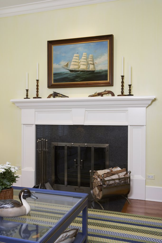 FAMILY ROOM: FIREPLACE DETAIL white painted mantel, pale yellow walls, nautical oil painting above mantel, antique revolvers, duck decoys, braided rug : Stock Photo