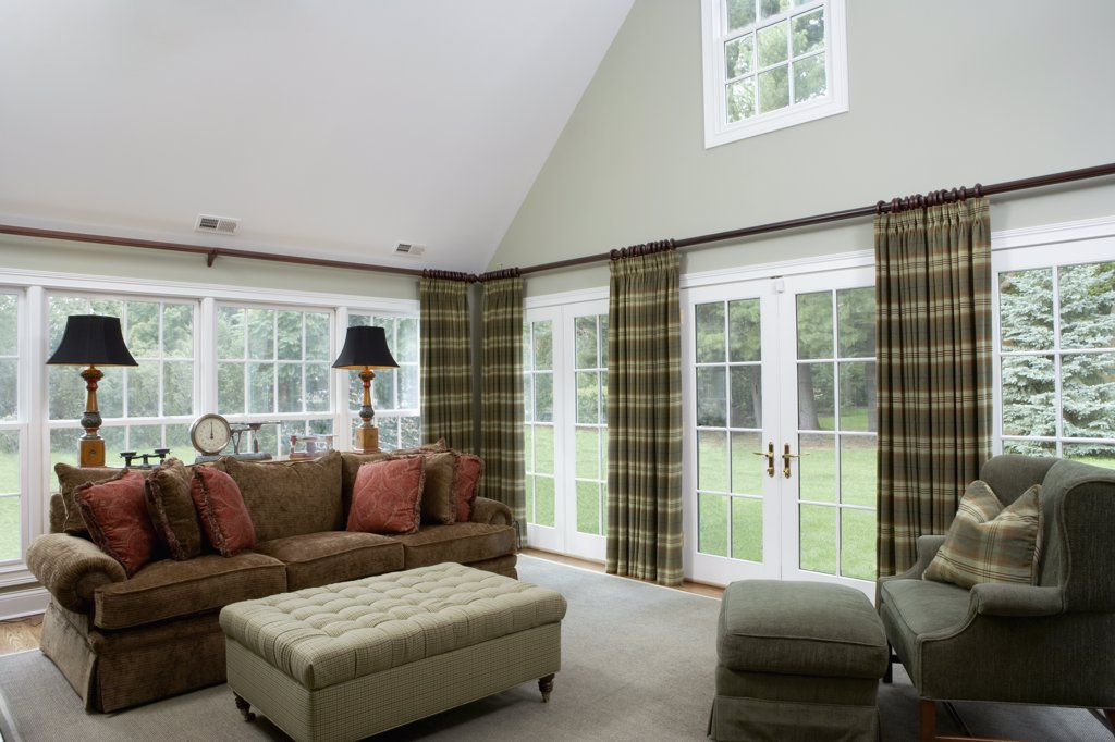 FAMILY ROOMS: Traditional high ceilings, French doors and long windows, continuous curtain rod, plaid curtains, earth tones, dark brown sofa, tufted ottoman, sofa table with antique scale collection , horizontal : Stock Photo