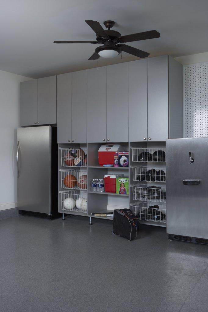 STORAGE: stainless steel refrigerator and beer kegger, wire pull out baskets with balls, shoes, sporting equipment, coolers, peg board, broom : Stock Photo